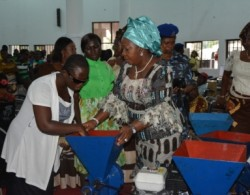 A blind woman receiving grinding machine from the wife of Abia state governor, Lady Mercy Odochi Orji at the event